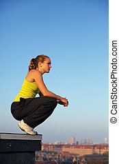 Traceur balancing on the corner edge of a high urban building in mental preparedness to participate in parkour.