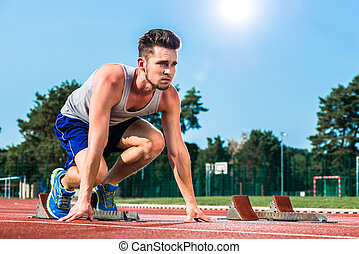 Track and field sprinter on starting point at cinder track...