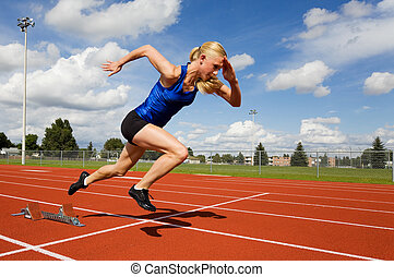 Track athlete exploding out of the starting blocks
