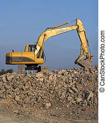 Large track hoe being used to fill dump trucks with rock to be used at differant types of construction sites like new housing sites, highways