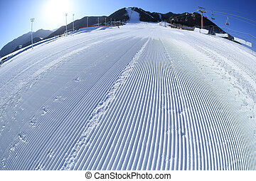 track lines on a slope left by a snowcat in ski resort