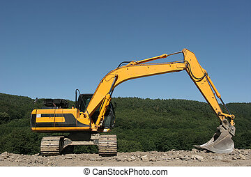 Yellow digger standing idle on hardcore, with trees and a blue sky to the rear.