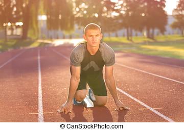 Track runner in starting position on sunny morning.