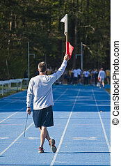 Track Starter - A man holding a flag about to start a track...
