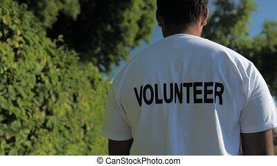 Trackig shot of a pleasant volunteer walking in the park -...