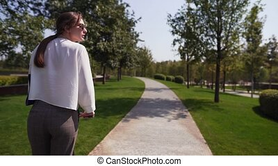 Tracking shot - a young girl in a white shirt is riding in a green park on a warm summer day. Trendy eco mode of transport 4k