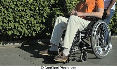 Tracking shot of a nice man walking with a wheelchaired man