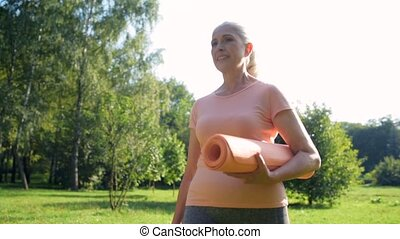 Tracking shot of a pleasant aged woman holding an exercise mat