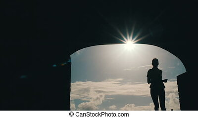 Camera moves in front of a woman silhouette jogging into a tunnel against beautiful sunlight.