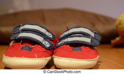 Tracking shot of baby shoes on the table - expecting baby...
