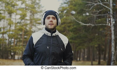 Tracking shot of Handsome runner man in headphones jogging while listening music in winter park in the morning