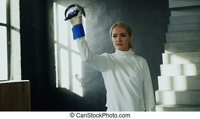 Tracking shot of Young concentrated fencer woman training...
