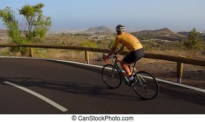 Tracking video shot of a male cyclist climbing up a mountain...