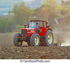 Tractor - A red tractor working on a field