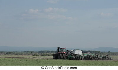 Tractor and Seeder Planting Crops. grass, trees field