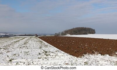 Tractor at work plowing a field in winter