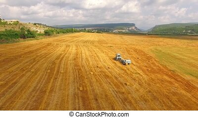 Tractor Baler Collecting Straw In Stubble Field