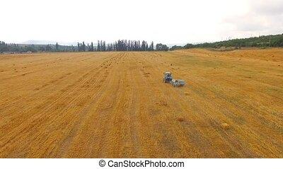 Tractor Baler Making Hay Bales In Stubble Field