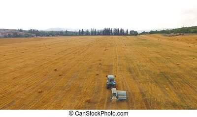 Tractor Baler Making Straw Bales In Stubble Field
