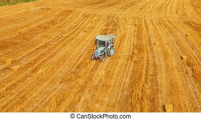 Tractor Baler Moving Across Yellow Stubble Field