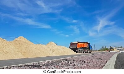 Tractor bucket loads heavy truck with sand - Heavy Tractor...