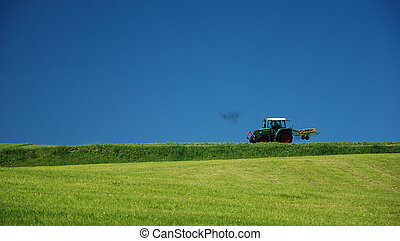 tractor cutting meadow in alps, Germany