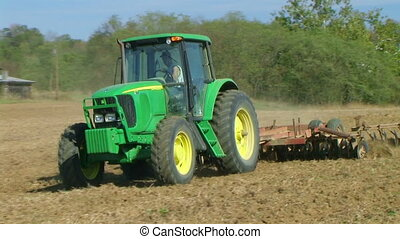 Tractor Discing Field - Tractor discing field with disc...