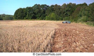 Tractor discing stubble field. Walking toward machine ...