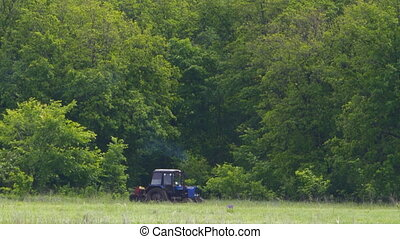 Tractor drives along the forest