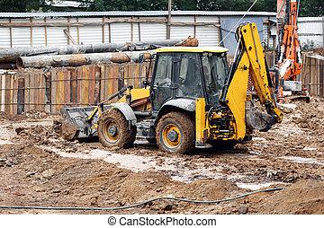 Tractor excavator with bucket rides running through mud...