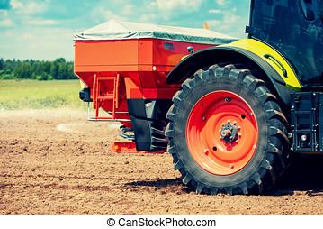 tractor fertilize the field with granular fertilizer