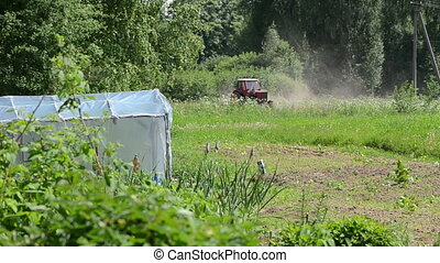 tractor field - old small red tractor harrow the ground at...