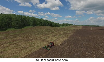 Tractor harvester on sowing. Late spring or early summer. Field. Green trees.