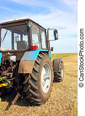 Tractor in a field, agricultural scene in summer