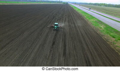 Tractor in a field making fertilizer