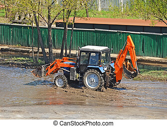 Tractor in a puddle on road construction site
