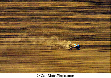 Tractor in field on a farm, aerial view - Harvester working ...