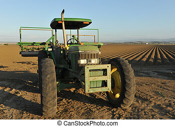 Tractor in front of a plowed field of dirt