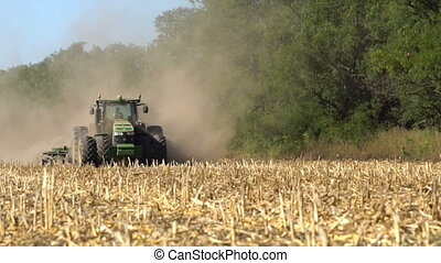 Tractor in the field with a harrow - Tractor in a field with...