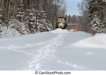 Tractor in the park clean snow-covered road