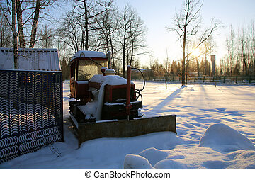 Tractor in the parking lot covered with snow
