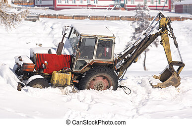 Tractor in the snow. Winter rural scene.