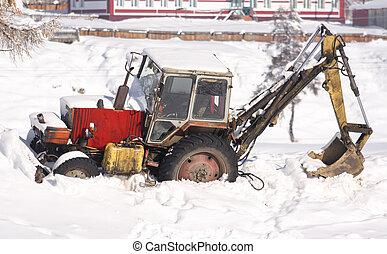Tractor in the snow. Winter rural scene.