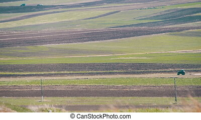 Tractor is Driving through the Field in the Mountains - A...