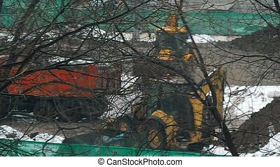 tractor is loading of truck on the construction site in the winter