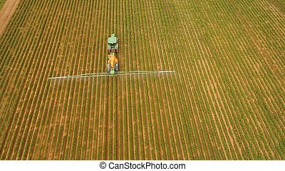 Tractor is spraying fertilizers field.