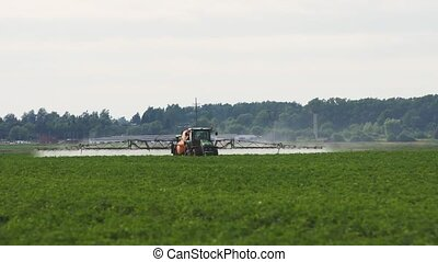 Tractor is spraying fertilizers field. - Aerial view tractor...