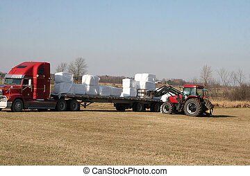 Tractor loading wrapped hay on trai