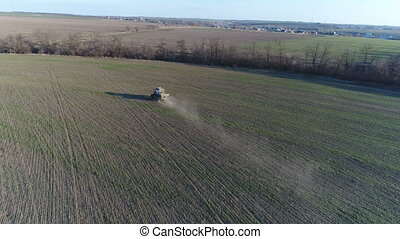Tractor makes fertilizer. Aerial survey - The tractor brings...
