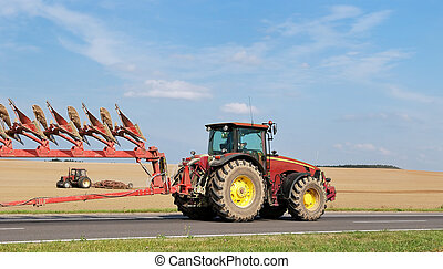 Tractor moving plough on the road - two tractors with...